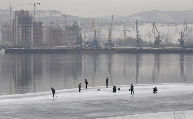 Men fish on the ice-covered Yenisei River in Krasnoyarsk, Russia March 21, 2018. REUTERS/Ilya Naymushin TPX IMAGES OF THE DAY