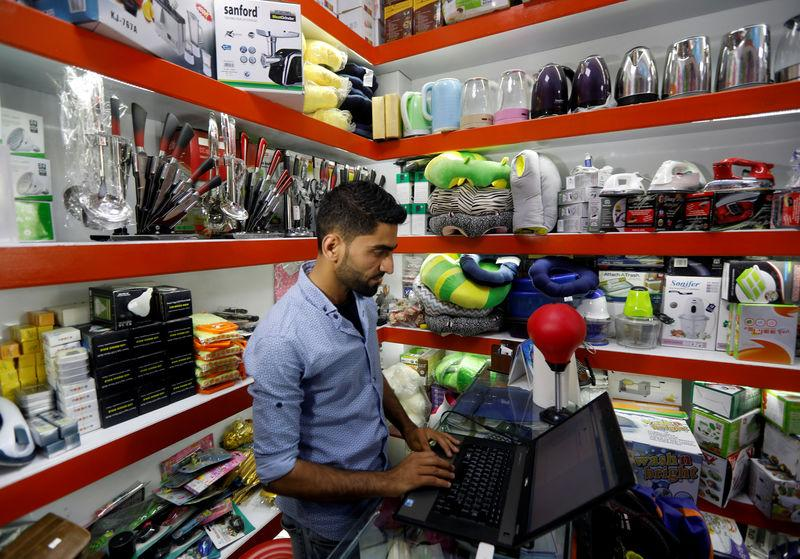 FILE PHOTO: An Afghan shopkeeper works on his laptop at his online shop in Kabul