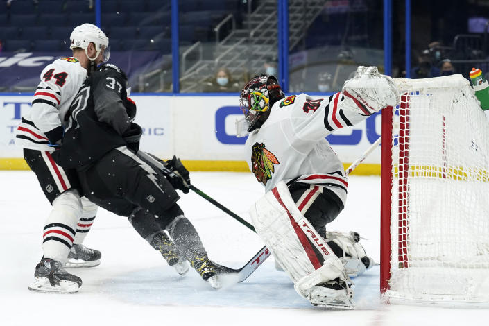Tampa Bay Lightning center Yanni Gourde (37) puts the puck past Chicago Blackhawks goaltender Malcolm Subban (30) for a goal during the second period of an NHL hockey game Saturday, March 20, 2021, in Tampa, Fla. Defending for Chicago is defenseman Calvin de Haan (44). (AP Photo/Chris O'Meara)
