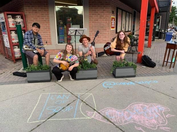 Can of Soup's Music Coordinator Brian Cho, Creative Director Mabel Wonnacott, Guest Artist Dylan Gowans and Administrative Coordinator Ellita Gagner performing at a pop-up event in Wortley Village.  (Submitted by Mabel Wonnacott - image credit)