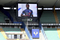 """Parma's Yann Karamoh wears a jersey with writing reading """"Keep racism out"""" as he is seen on a giant screen broadcasting a video of players from all 20 Serie A clubs and all sorts of backgrounds delivering a strong message of inclusion before a Serie A match between Verona and Atalanta at the Bentegodi stadium in Verona, Italy, Sunday, March 21, 2021. Serie A's efforts to combat racism inside its stadiums was in shambles little more than a year ago when league CEO Luigi De Siervo decided to take matters into his own hands. (Paola Garbuio/LaPresse via AP)"""