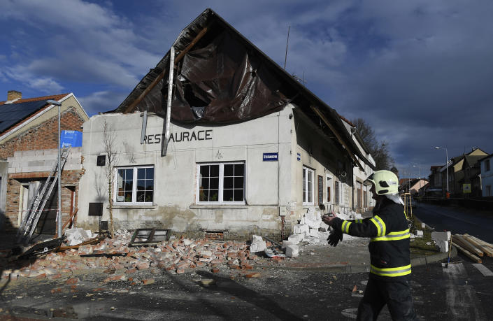 A fireman passes by a house which roof was moved due to a strong storm in Kladno, Czech Republic, Monday, Feb. 10, 2020. A storm battered the U.K. and northern Europe with hurricane-force winds and heavy rains Sunday, halting flights and trains and producing heaving seas that closed down ports. Soccer games, farmers' markets and cultural events were canceled as authorities urged millions of people to stay indoors, away from falling tree branches. (Ondrej Deml/CTK via AP)