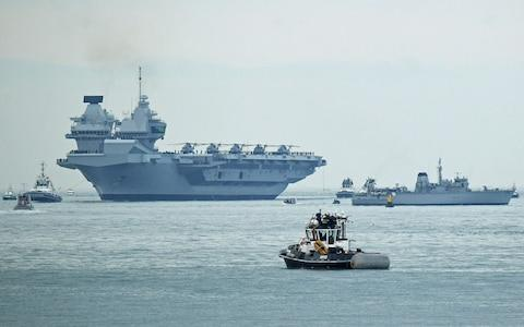 A flotilla of craft follow HMS Queen Elizabeth as she sails into the Solent - Credit: Victoria Jones/PA