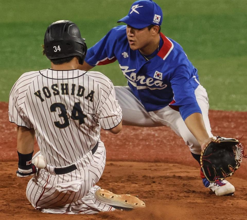Japan's Masataka Yoshida is hit by the ball as he slides safely into second base in front of South Korea's Jaegyun Hwang.