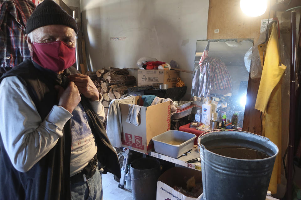 Raymond Clark stands in front of his makeshift washing station in his home in Teesto, Arizona, on the Navajo Nation on Thursday, Feb. 11, 2021. Teesto workers, health representatives, volunteers and neighbors keep close tabs on another to ensure the most vulnerable citizens get the help they need. (AP Photo/Felicia Fonseca)