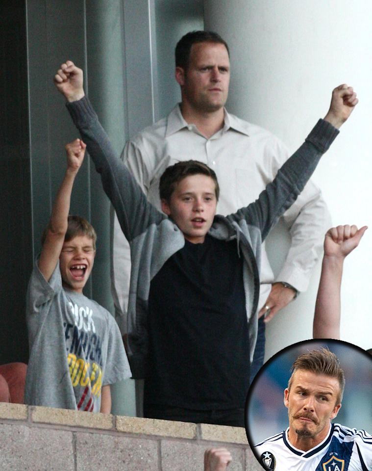 "Goal! Pro soccer player David Beckham brought two of his biggest fans <span style=""font-size:11.0pt; "">–</span> sons (L-R) Brooklyn, 13, and Romeo, 9 <span style=""font-size:11.0pt; "">–</span> along for good luck when his team, the Los Angeles Galaxy, recently took on the Vancouver Whitecaps in Carson, California. The boys (whose mom, Victoria, 7-year-old brother Cruz, and baby sister Harper sat this one out) were plenty enthusiastic: staying on their feet throughout much of the game, waving their arms wildly, and  cheering on No. 23. The Galaxy won 3-0. Who needs the Olympics anyway? (6/23/2012)"