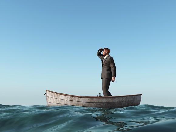 Man standing in the middle of a small boat in the ocean, looking out into the distance.