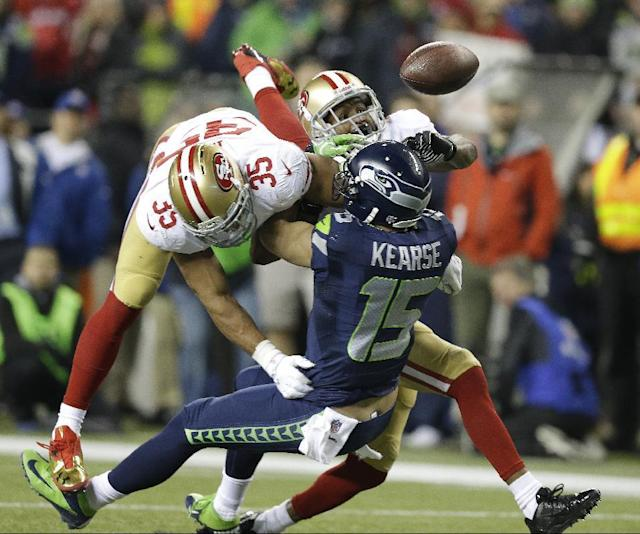 San Francisco 49ers' Eric Reid (35) and Donte Whitner (31) break up a pass intended for Seattle Seahawks' Jermaine Kearse during the second half of the NFL football NFC Championship game Sunday, Jan. 19, 2014, in Seattle. (AP Photo/Elaine Thompson)