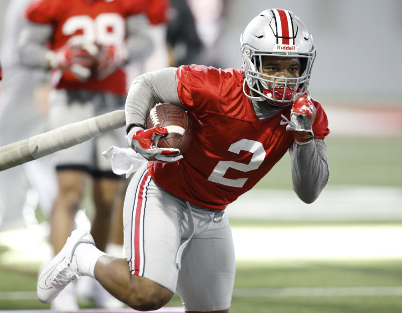 """FILE - In this Wednesday, March 6, 2019 file photo, Ohio State running back J.K. Dobbins runs through a drill during an NCAA college football practice in Columbus, Ohio. J.K. Dobbins wants to make up for his """"failure"""" last season. Despite rushing for over 1,000 yards, Dobbins calls 2018 a disappointment. He had a drop-off from his record-breaking freshman year and is determined to get back to that level and prove he's best running back in the nation.(AP Photo/Paul Vernon, File)"""