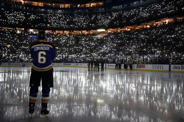 FILE - In this Dec. 1, 2017, file photo, St. Louis Blues' Joel Edmundson pauses as fans use their phones to light up Scottrade Center during a ceremony as part of a league-wide cancer awareness campaign, before an NHL hockey game between the St. Louis Blues and the Los Angeles Kings in St. Louis. When the virus wanes enough to allow the games to begin again, the very essence of these events will likely be missing. Playing in empty buildings would require a significant recalibration. (AP Photo/Jeff Roberson, File)
