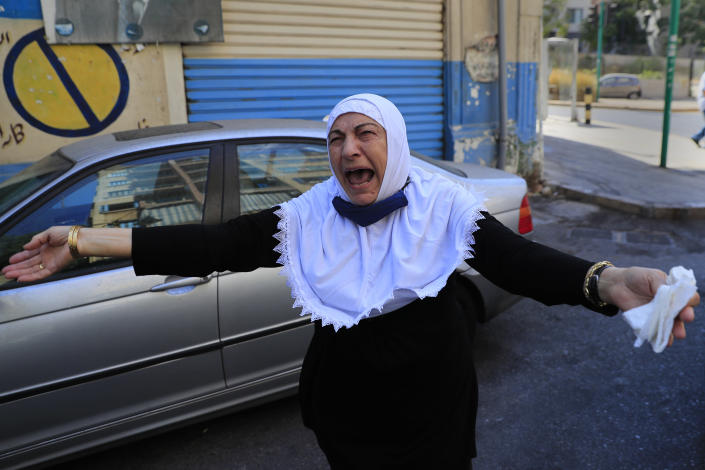 The aunt of Ibrahim Harb, 35, a Lebanese man who was critically injured in the massive explosion at Beirut's port last year and who died on Monday evening nearly 14 months after the blast, mourns during his funeral procession, in Beirut, Lebanon, Tuesday, Sept. 28, 2021. On August 4, 2020, hundreds of tons of ammonium nitrate, a highly explosive material used in fertilizers, ignited after a massive fire at the port. The death brings to at least 215 the number of people who have been killed by the blast, according to official records. (AP Photo/Hussein Malla)