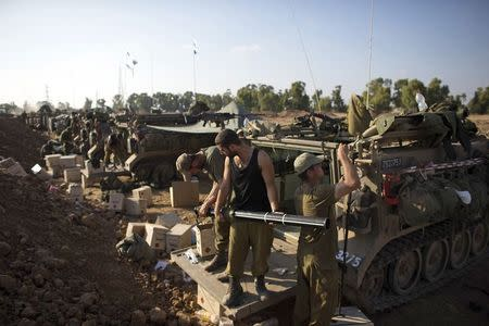 Israeli soldiers prepare armoured personnel carriers (APCs) at a staging area outside the northern Gaza Strip July 27, 2014. REUTERS/Ronen Zvulun