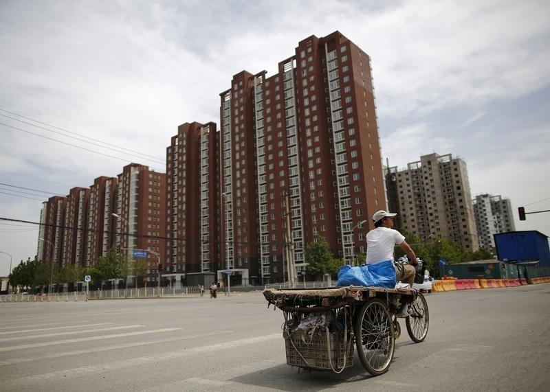 A garbage collector rides his tricycle as he looks for recyclable items on the streets of Beijing