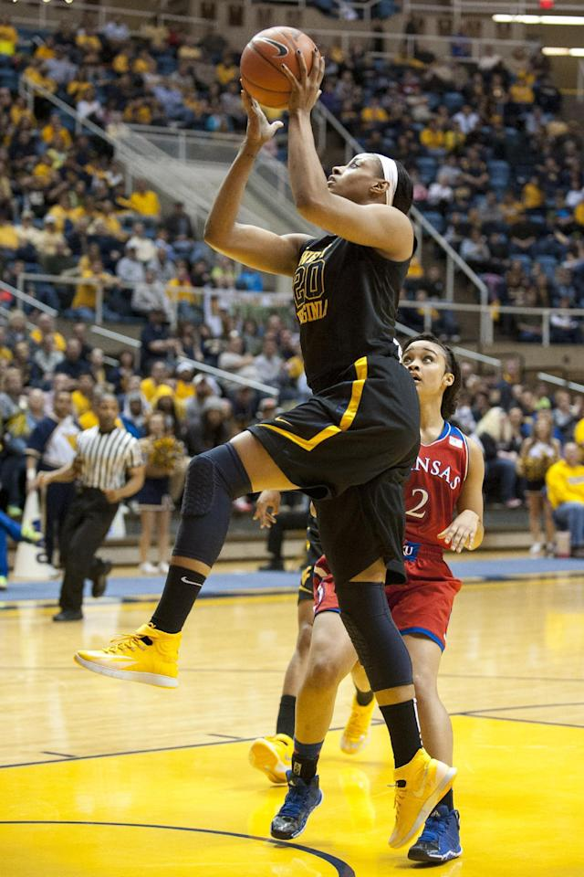West Virginia's Asya Bussie (20) drives to the basket during the first half of an NCAA college basketball game against Kansas, Tuesday, March 4, 2014, in Morgantown, W.Va. (AP Photo/Andrew Ferguson)