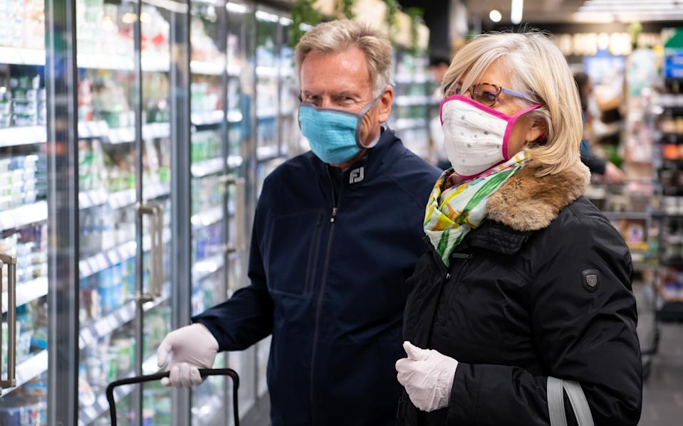 01 April 2020, Bavaria, Neubiberg: A man and a woman wear a mouthguard when shopping in a supermarket. Photo: Sven Hoppe/dpa (Photo by Sven Hoppe/picture alliance via Getty Images)