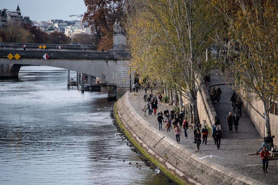 People walk on the banks of the Seine river, on November 14, 2020 in Paris, amid the second lockdown.