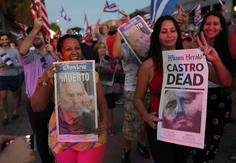 People hold posters printed by El Nuevo Herald and Miami Herald with a headline that reads that the former Cuban President Fidel Castro is dead as they react to the news of his death outside the restaurant Versailles on November 26, 2016 in Miami (AFP Photo/Joe Raedle)