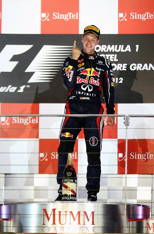 SINGAPORE - SEPTEMBER 23:  Sebastian Vettel of Germany and Red Bull Racing celebrates on the podium after winning the Singapore Formula One Grand Prix at the Marina Bay Street Circuit on September 23, 2012 in Singapore, Singapore.  (Photo by Mark Thompson/Getty Images)