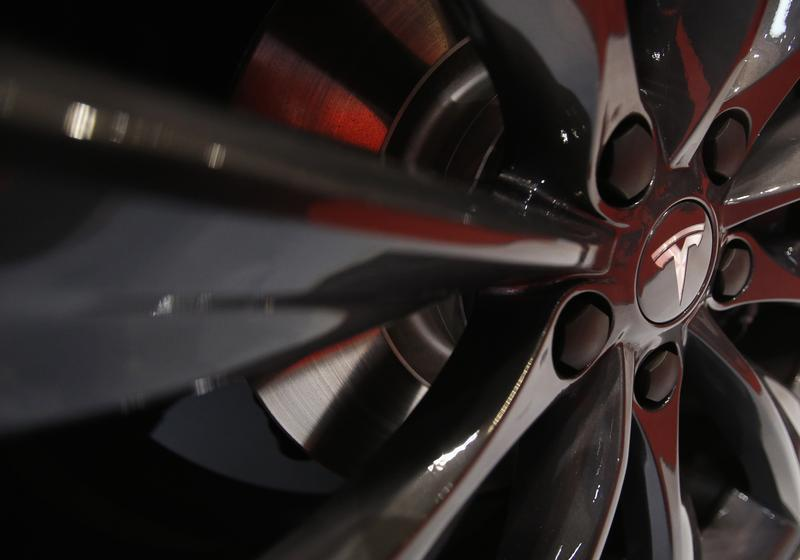 A logo of Tesla Motor Inc is seen on the wheel of its Model S car, on display at the 43rd Tokyo Motor Show