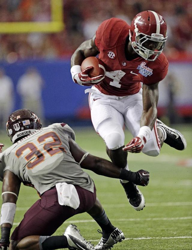 Alabama running back T.J. Yeldon (4) jumps over the tackle of Virginia Tech linebacker Josh Trimble (32) in the first half of an NCAA college football game, Saturday, Aug. 31, 2013, in Atlanta. (AP Photo/Dave Martin)