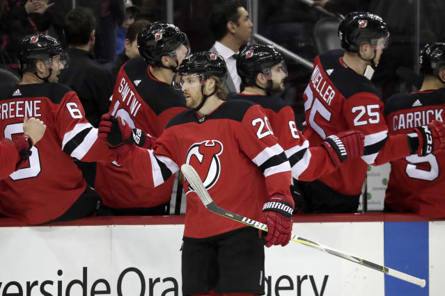 New Jersey Devils center Blake Coleman (20) swings by the bench after scoring a goal on the Buffalo Sabres during the first period of an NHL hockey game, Monday, March 25, 2019, in Newark, N.J. (AP Photo/Julio Cortez)