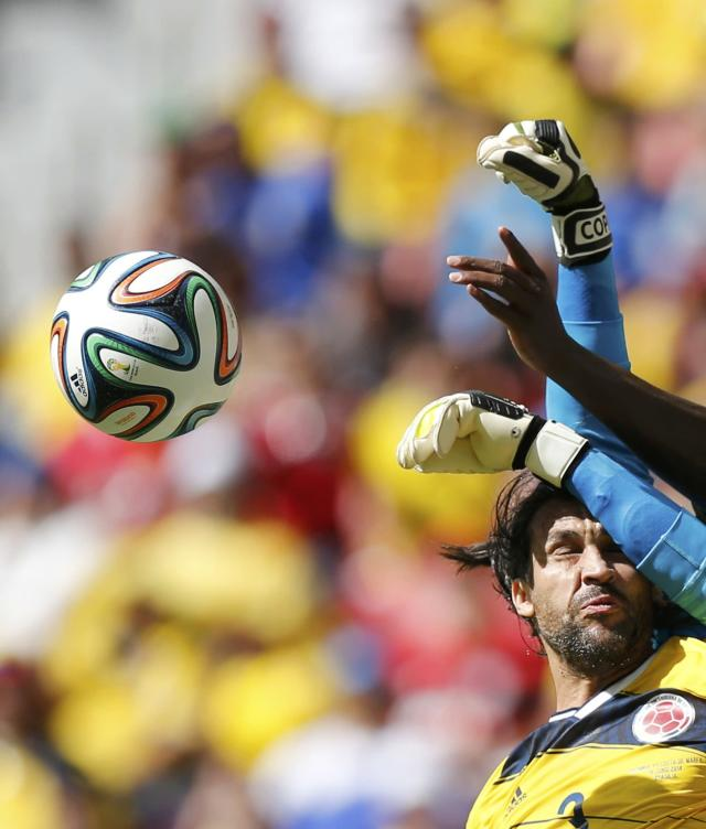 Colombia's Mario Yepes reacts as he fights for the ball with Ivory Coast's goalkeeper Boubacar Barry (blue) during their 2014 World Cup Group C soccer match at the Brasilia national stadium in Brasilia June 19, 2014. REUTERS/Ueslei Marcelino (BRAZIL - Tags: SOCCER SPORT WORLD CUP TPX IMAGES OF THE DAY)