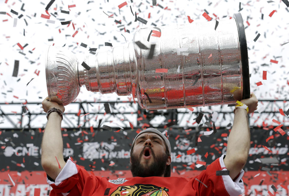 FILE - Chicago Blackhawks defenseman Brent Seabrook celebrates as he holds up the Stanley Cup Trophy during a rally at Soldier Field for the NHL Stanley Cup hockey champions, in Chicago, in this Thursday, June 18, 2015, file photo. Longtime Chicago Blackhawks defenseman and three-time Stanley Cup winner Brent Seabrook announced Friday, March 5, 2021, he's unable to continue playing hockey because of injury. (AP Photo/Nam Y. Huh, File)