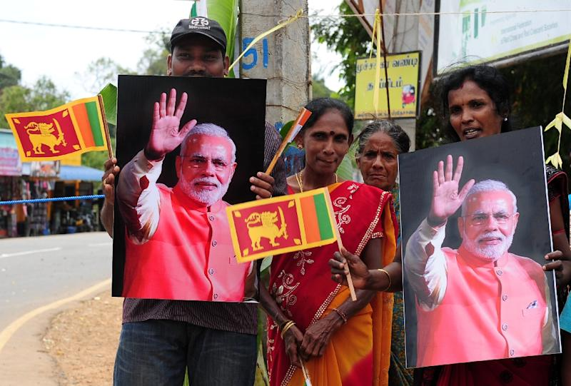 Sri Lankan ethnic Tamils hold a portrait of Indian Prime Minister Narendra Modi as they wait for his arrival at a ceremony in Jaffna, on March 14, 2015 (AFP Photo/Lakruwan Wanniarachchi)
