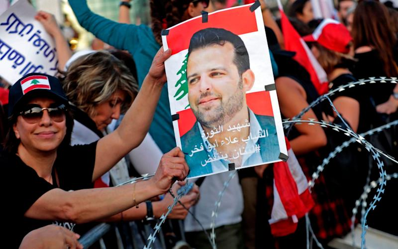 A Lebanese demonstrator carries a portrait of Alaa Abou Fakhr, who was shot dead south of Beirut - AFP