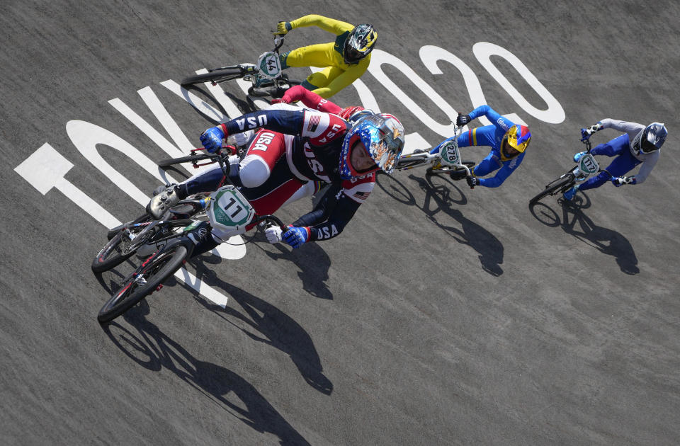 Connor Fields of the United States, center, leads with Anthony Dean of Australia, above, Carlos Alberto Ramirez Yepes of Colombia, 2nd right, and Giacomo Fantoni of Italy, right, following, in the men's BMX Racing quarterfinals at the 2020 Summer Olympics, Thursday, July 29, 2021, in Tokyo, Japan. (AP Photo/Ben Curtis)