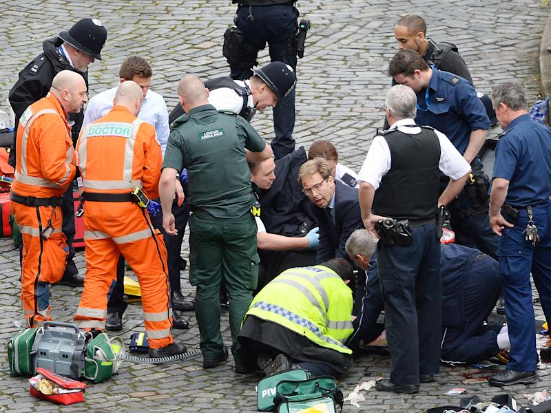 Conservative MP Tobias Ellwood (centre) helps emergency services attend to a police officer outside the Palace of Westminster, London, after a policeman was stabbed and his apparent attacker shot by officers in a major security incident at the Houses of Parliament: PA wire