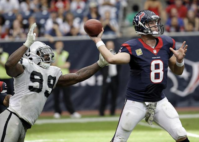 Houston Texans' Matt Schaub throws while being rushed by Oakland Raiders' Lamarr Houston (99) during the second half of an NFL football game Sunday, Nov. 17, 2013, in Houston. (AP Photo/Morry Gash)