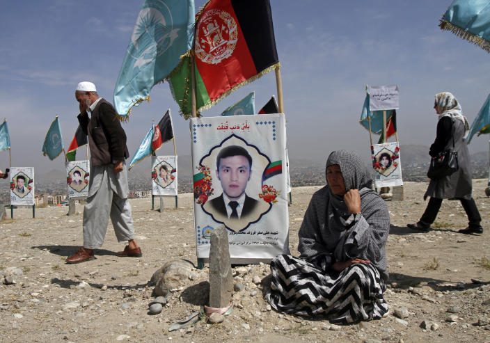 An Afghan woman sits next to the grave of her son, adorned with his picture, on the outskirts of Kabul, Afghanistan, Monday, Sept 14, 2020. Scores of friends and families of students who were killed in local conflicts are gathering in a cemetery to call for a permanent countrywide ceasefire from the parties to the intra-Afghan peace conference taking place in Doha, Qatar. (AP Photo/Rahmat Gul)