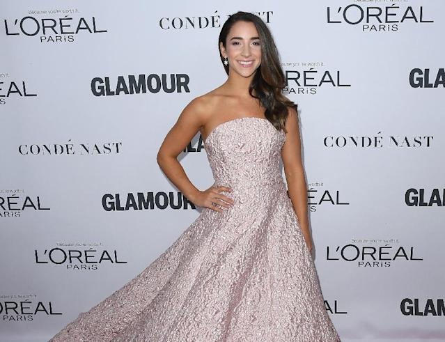 """Olympic gymnast Aly Raisman, who is dedicating her time to fighting sexual abuse, is shown posing with the words """"survivor"""" across her chest in the Sports Illustrated Swimsuit Issue (AFP Photo/ANGELA WEISS)"""