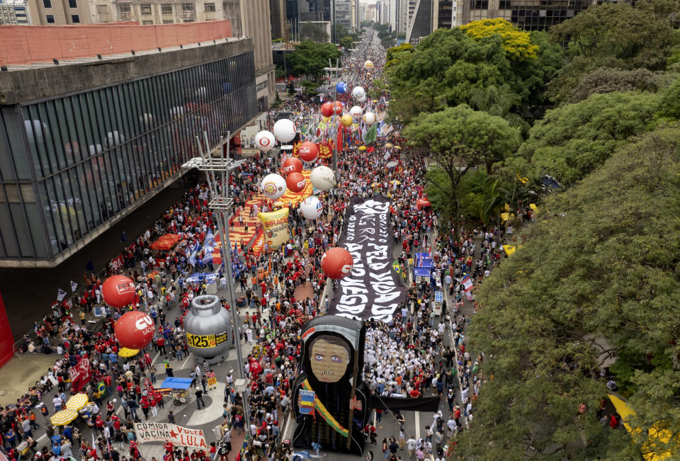 Demonstrators gather next to a large inflatable doll depicting Brazilian President Jair Bolsonaro during a protest against him, calling for his impeachment over his government handling of the pandemic and accusations of corruption in the purchases of COVID-19 vaccines in Sao Paulo, Brazil, Saturday, Oct. 2, 2021. (AP Photo/Andre Penner)