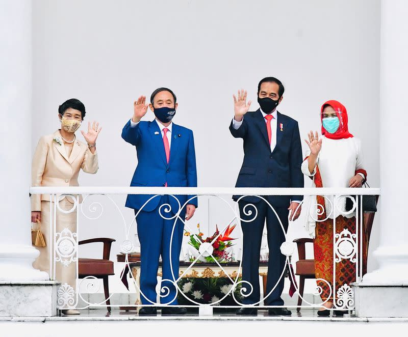 Japan's PM Suga, Indonesian President Widodo and their wives wave during a visit at Indonesian Presidential Palace in Bogor