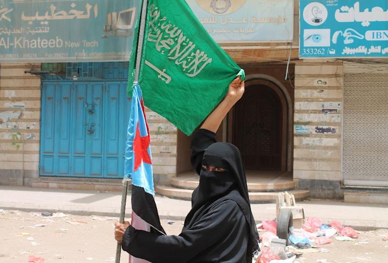 A Yemeni woman holds a Saudi flag and a Yemeni southern separatist movement flag in Aden on April 9, 2015, in support of the Saudi-led coalition air war against Shiite Huthi militia (AFP Photo/Saleh al-Obeidi)