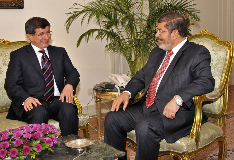 FILE - In Monday, Sept. 17, 2012 file photo released by the Egyptian President, Egyptian President Mohammed Morsi, right, meets with Turkish Foreign Minister Ahmet Davutoglu at the Presidential Palace in Cairo, Egypt. The question of who speaks for the Middle East, which is chronically prone to turmoil, has no easy answer. There is a sectarian rift, a divide over tradition and modernity, and a divide over secularism and religion. Amid this cacophony, Turkey and Egypt, both with claims to regional leadership, are seeking a closer partnership even though their visions and circumstances differ starkly.(AP Photo/Egyptian Presidency, File)