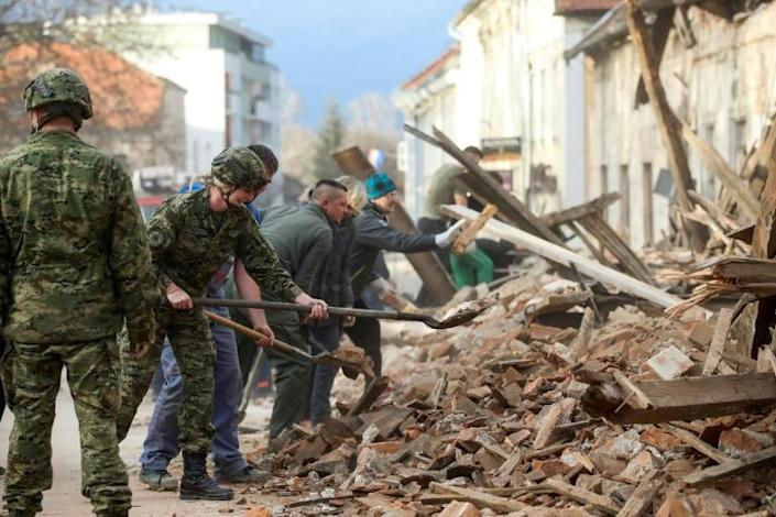 Croatian soldiers and people clean rubble next to damaged buildings in Petrinja