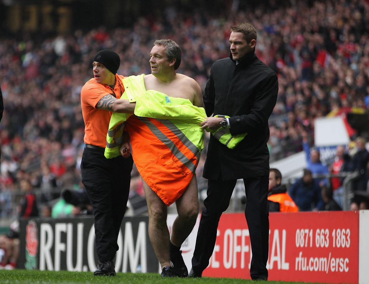 LONDON, ENGLAND - APRIL 28:  A streaker is led away during the Babcock Trophy match between the Army and the Navy at Twickenham Stadium on April 28, 2012 in London, England.  (Photo by Tom Shaw/Getty Images)