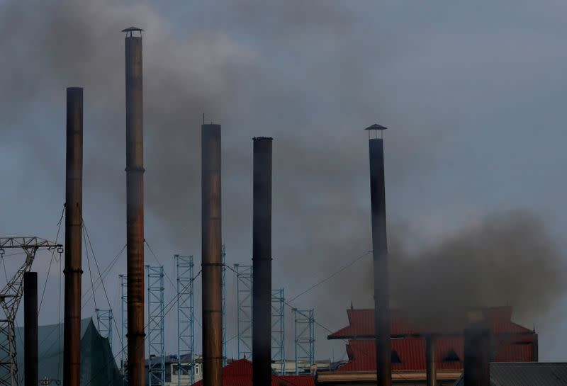 FILE PHOTO: Smoke rises from the chimney of a paper factory outside Hanoi