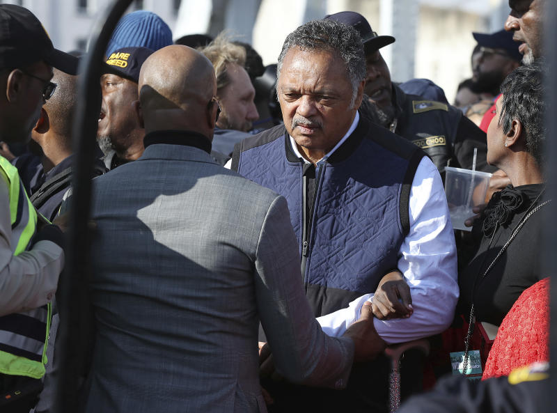 The Rev. Jesse Jackson is helped across the Edmund Pettus Bridge, Sunday, March 1, 2020, in Selma, Ala. (Curtis Compton/Atlanta Journal-Constitution via AP)