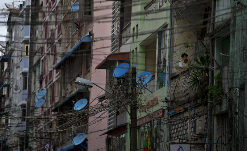 In this June 24, 2013 photo, a man uses a mobile phone while standing on a balcony of an apartment as telephone and electricity cables dangle in the foreground in Yangon, Myanmar. Foreign companies will tap into one of the world's final telecom frontiers Thursday, June 27, 2013, when Myanmar hands out licenses to operate two new mobile phone networks — part of efforts by the long-isolated nation to use technology to spur economic development. (AP Photo/Gemunu Amarasinghe)