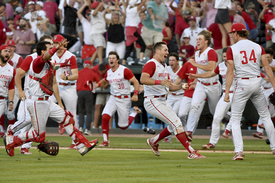 North Carolina State players celebrate after beating Arkansas 3-2 to advance to the College World Series during an NCAA college baseball super regional game Sunday, June 13, 2021, in Fayetteville, Ark. (AP Photo/Michael Woods)