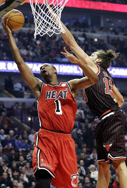 Miami Heat center Chris Bosh (1) drives to the basket against Chicago Bulls center Joakim Noah during the first half of an NBA basketball game in Chicago, Thursday, Feb. 21, 2013. (AP Photo/Nam Y. Huh)
