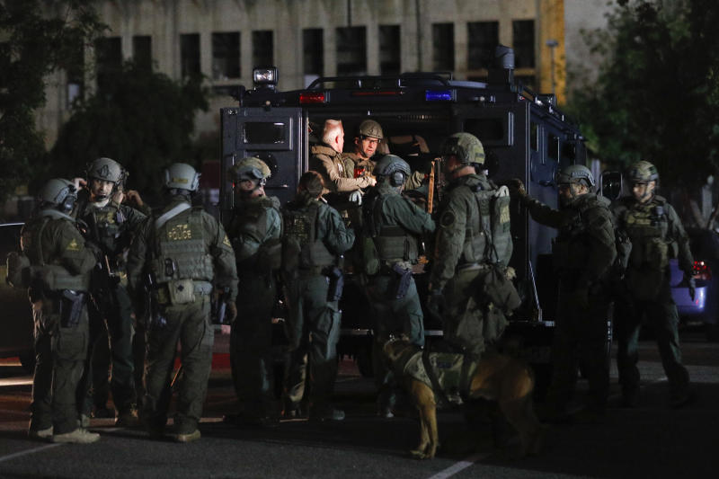 ATF agents prepare for a raid in the parking lot of the Los Angeles Memorial Coliseum early Wednesday morning, May 17, 2017, in Los Angeles. Hundreds of federal and local law enforcement fanned out across Los Angeles, serving arrest and search warrants as part of a three-year investigation into the violent and brutal street gang MS-13. (AP Photo/Jae C. Hong)