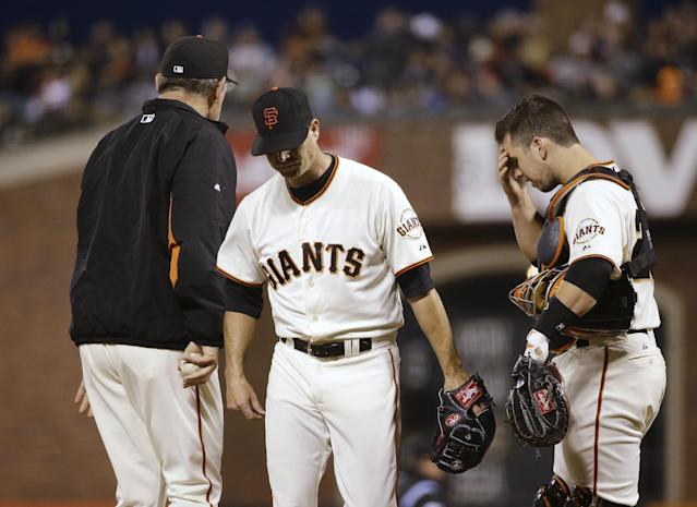 San Francisco Giants starting pitcher Tim Hudson, center, walks to the dugout after being taken out of the baseball game by manager Bruce Bochy, left, as catcher Buster Posey, right, waits during the sixth inning Tuesday, June 24, 2014, in San Francisco. (AP Photo/Eric Risberg)
