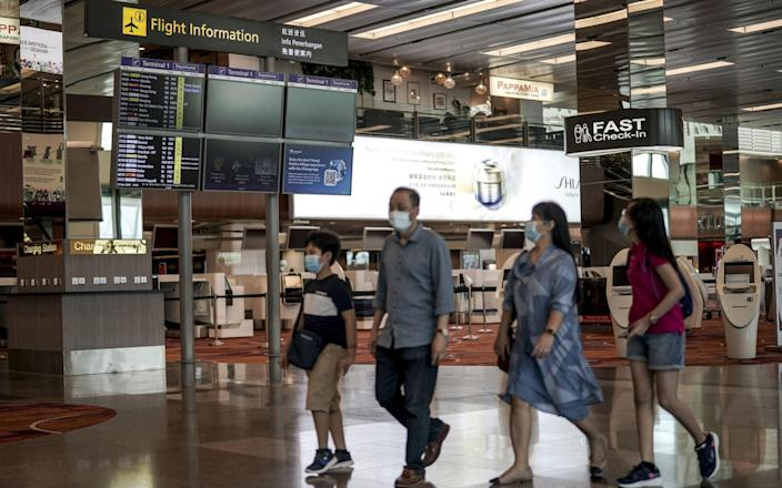 A family walks through the departure hall of the Changi Airport in Singapore - EPA