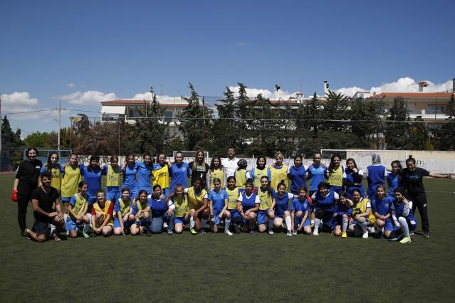 In this Thursday, May 2, 2019 photo, members Hestia FC Women's Refugee Soccer and AO Vrilission players pose for a photograph before a friendly game in Athens. Many of the players at Hestia FC weren't allowed to play or even watch soccer matches in their home countries. Hestia FC was set up by the Olympic Truce Centre, a non-government organization created in 2000 by the International Olympic Committee and Greek Foreign Ministry. (AP Photo/Thanassis Stavrakis)