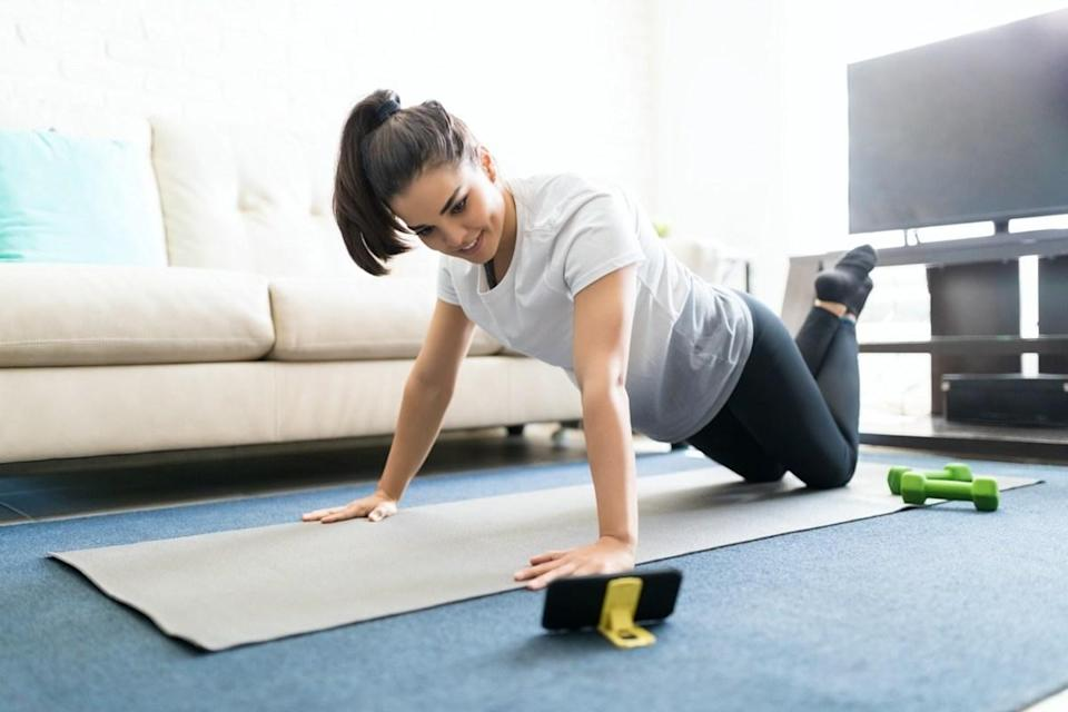 woman learning new exercises watching online workout tutorials over her phone at home